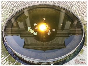 Image of a circular shaped fountain filled with water. In the water there is a reflection of a building, upside down and the yellow sunshine in the centre.