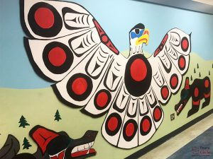 Image of wall with an indigenous peace of artwork. A mostly black, red and white patterned coloured eagle on a background of blue and green.